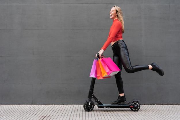 Chica en scooter eléctrico con bolsas de compras Foto gratis