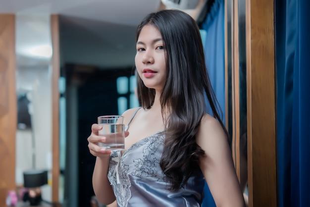 Chica sexy en el hotel, feliz hermosa joven bebiendo agua Foto gratis