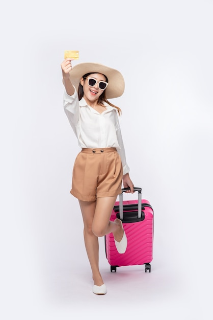 Chica con sombrero con tarjeta de crédito y maleta para viajar Foto gratis