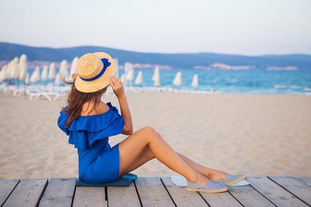 556888387798 Chica con sombrero y vestido azul sentada en una playa de arena ...