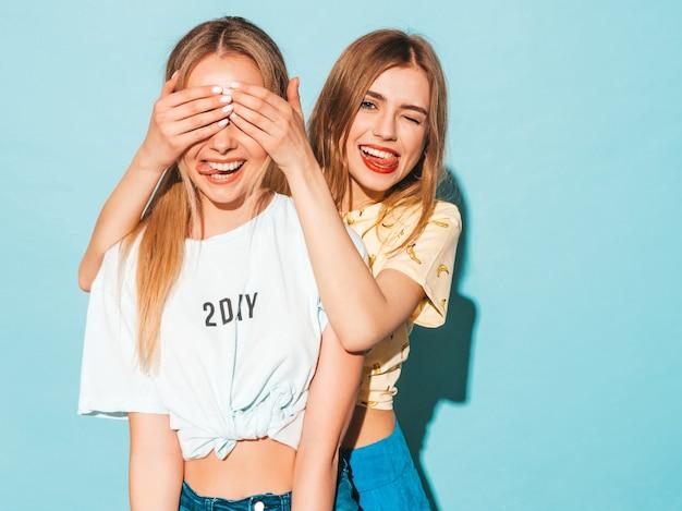 Chica sorprende a su mejor amiga. modelo cubriéndose los ojos y abrazándose por detrás. Foto gratis