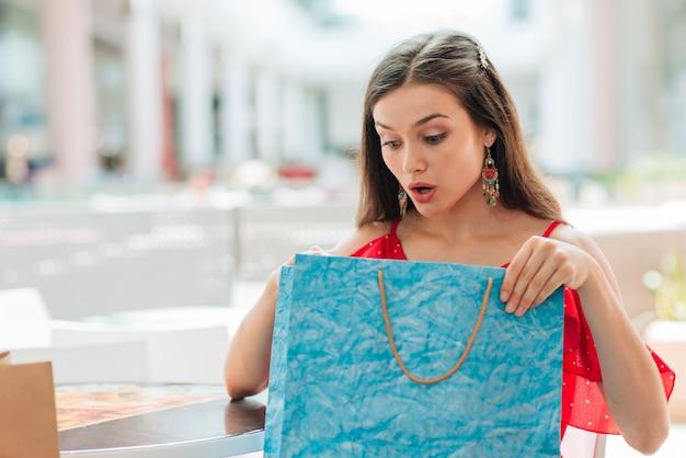 Chica sorprendida revisando su ropa nueva Foto gratis