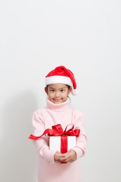 Chica sosteniendo una caja de regalo en suéter y gorro de papá noel Foto Premium