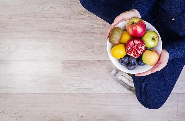 Chica sosteniendo un plato blanco con manzanas, ciruelas, kiwi y granada. alimentación saludable. Foto Premium