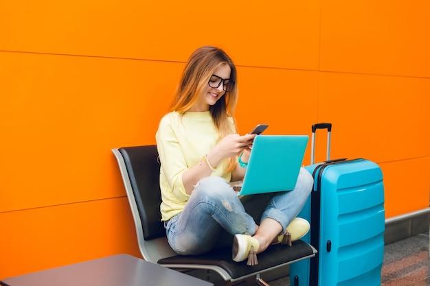 Chica en suéter amarillo y jeans azul está sentada en una silla sobre fondo naranja. ella tiene una maleta grande cerca y una computadora portátil en las rodillas. ella está escribiendo en el teléfono. Foto gratis