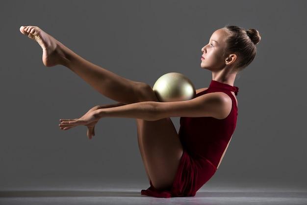 Chica sujetando una pelota con sus rodillas y pecho Foto gratis