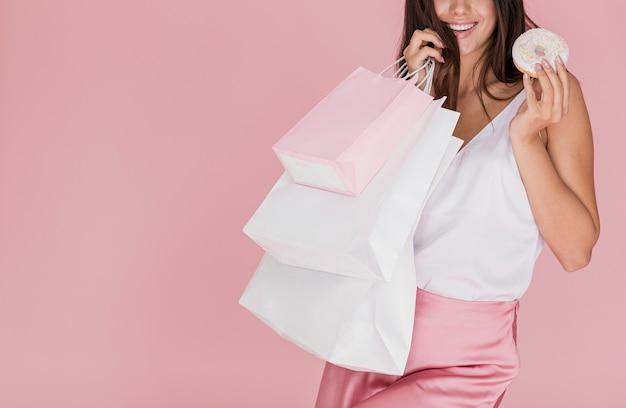 Chica sujetando una rosquilla y redes de compra Foto gratis