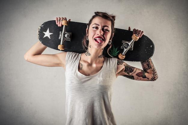 Chica tatuada con estilo con un monopatín Foto Premium