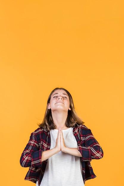 La chica de tiro medio da la posición de oración. Foto gratis