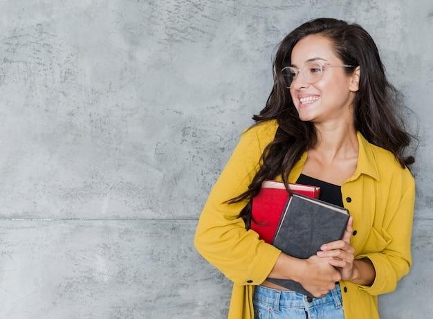 Chica de tiro medio con libros y fondo de cemento Foto gratis