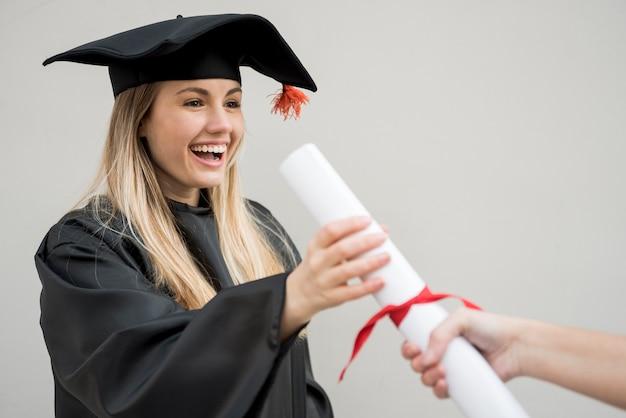 Chica de tiro medio obteniendo su certificado de universidad Foto gratis