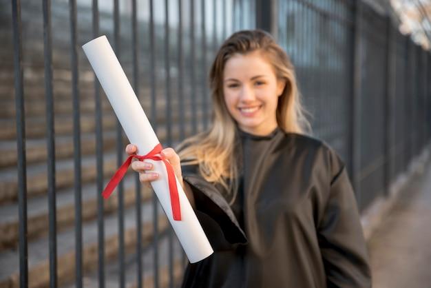 Chica de tiro medio sonriendo sosteniendo su certificado Foto gratis