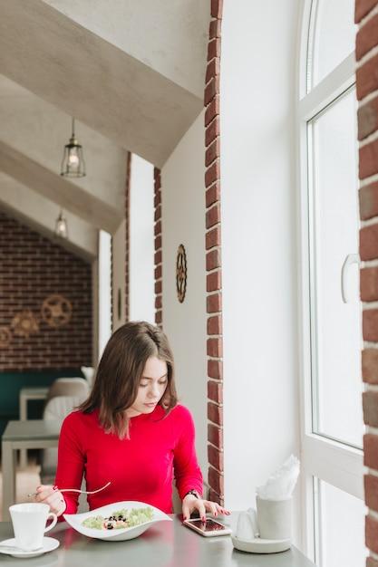 Chica tomando café en un restaurante Foto gratis