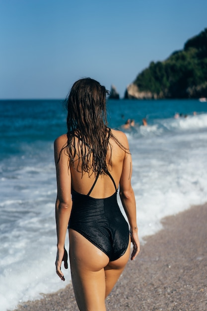 La chica en traje de baño negro junto al mar. vista trasera. Foto gratis