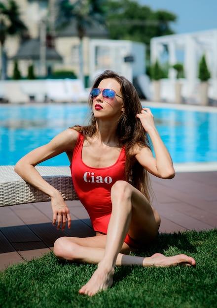 Chica en traje de baño rojo se sienta por la piscina azul ...