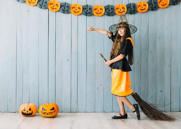 Chica en traje de bruja de pie con escoba Foto gratis