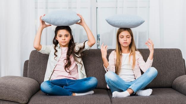 Chica tratando de hacer yoga como su amiga mediando en un sofá con cojín Foto gratis