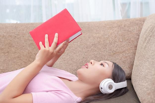 Chica tumbada en el sofá escuchando música y leyendo libros. Foto gratis