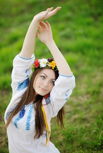 Chica ucraniana con una camisa y una corona de flores en su cabeza. Foto Premium