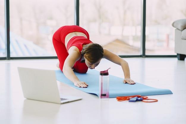 Chica en uniforme deportivo rojo practicando yoga en casa Foto gratis