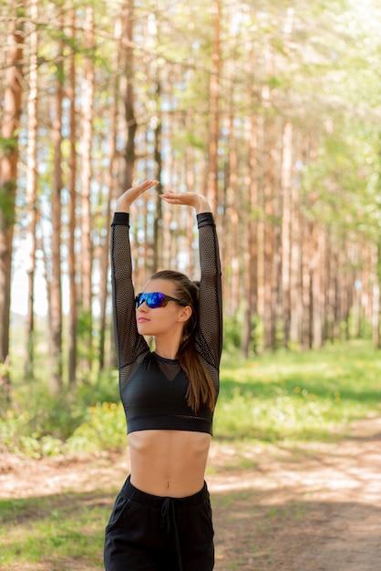 Chica en uniforme y gafas de sol haciendo deporte en un parque Foto Premium
