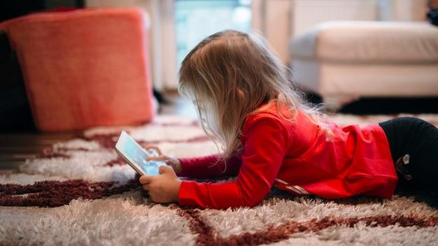 Chica usando tableta en la alfombra Foto gratis