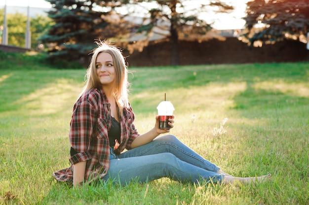 Chica con un vaso de jugo en un prado verde. Foto Premium
