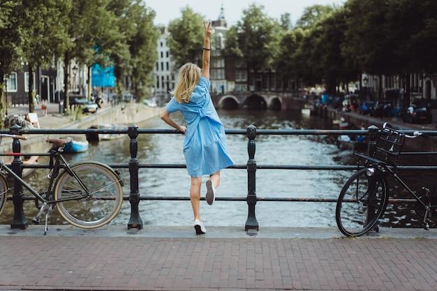 Chica en un vestido azul en el puente en amsterdam Foto gratis