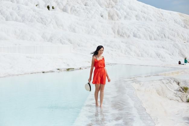 Chica En Vestido Rojo Sobre Travertinos Blancos Agua Foto