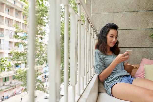 Chica vietnamita atractiva enviando mensajes de texto y tomando té en el balcón Foto gratis