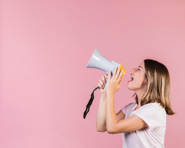 Chica de vista lateral gritando en un megáfono Foto Premium