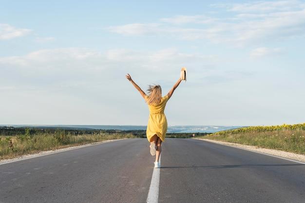 Chica de vista trasera corriendo en medio de la calle Foto gratis