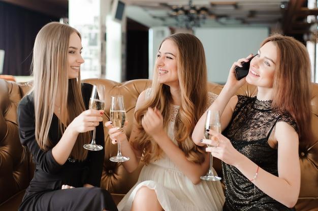 Chicas alegres tintineando copas de champán en la fiesta Foto Premium