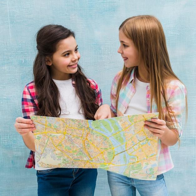 Chicas Bonitas Sosteniendo Un Mapa En La Mano Mirando El Uno