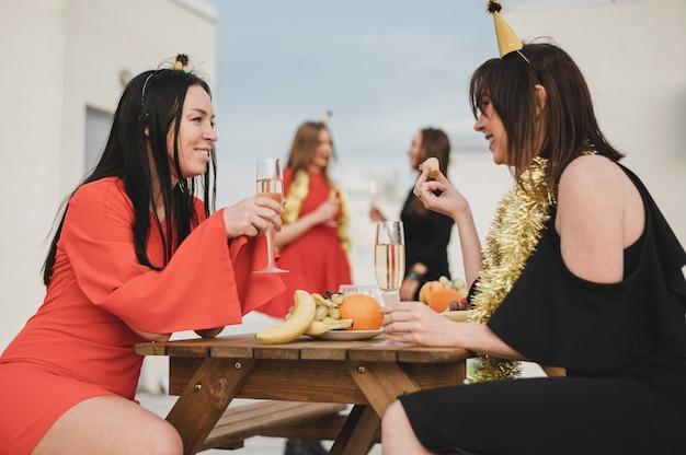 Chicas divirtiéndose en una fiesta en la azotea Foto gratis