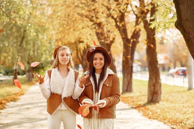 Chicas elegantes y con estilo en un parque de otoño Foto gratis