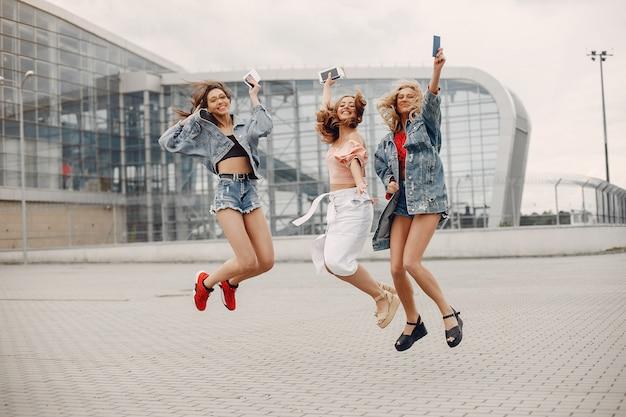 Chicas elegantes y con estilo de pie cerca del aeropuerto Foto gratis