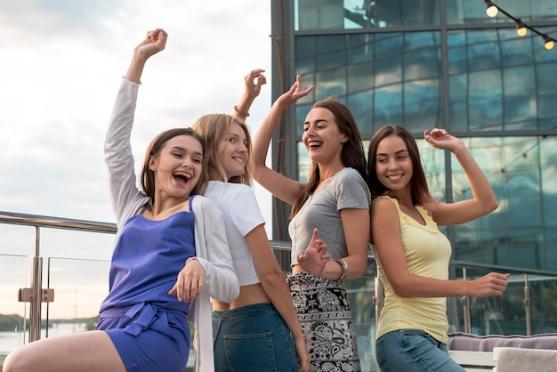 Chicas felices bailando espalda con espalda Foto gratis