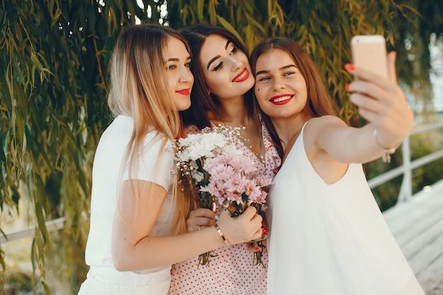 Chicas guapas en un parque de verano con un teléfono. Foto gratis