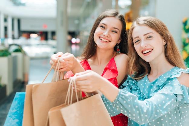 Chicas guapas posando con bolsas de la compra. Foto gratis