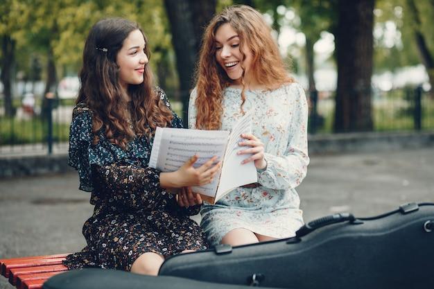 Chicas hermosas y románticas en un parque con un violín Foto gratis