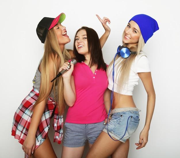 Chicas hipster de belleza con un micrófono cantando y divirtiéndose Foto Premium