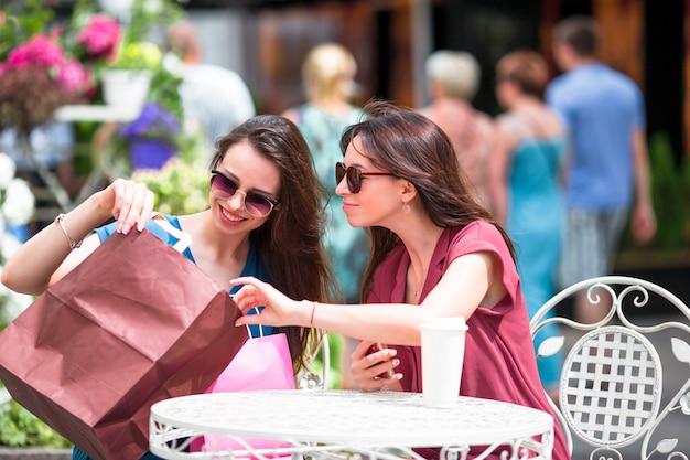 Chicas jóvenes de moda con bolsas de compras en el café al aire libre. venta, consumismo y concepto de personas. Foto Premium