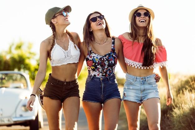 af5189070c Chicas jóvenes riendo con pantalones cortos y gafas de sol Foto Premium