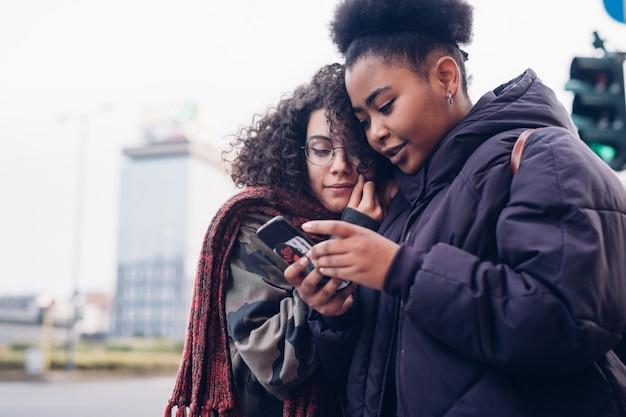 Chicas jóvenes con smartphone en la ciudad Foto Premium