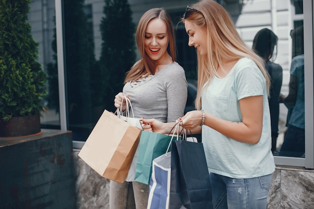Chicas lindas con bolsa de compras en una ciudad. Foto gratis