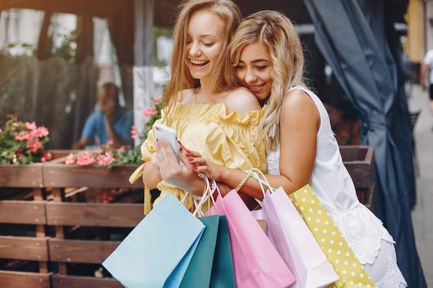 Chicas lindas con bolsa de compras en una ciudad Foto gratis