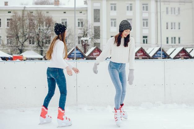 Chicas lindas y hermosas en un suéter blanco en una ciudad de invierno Foto gratis