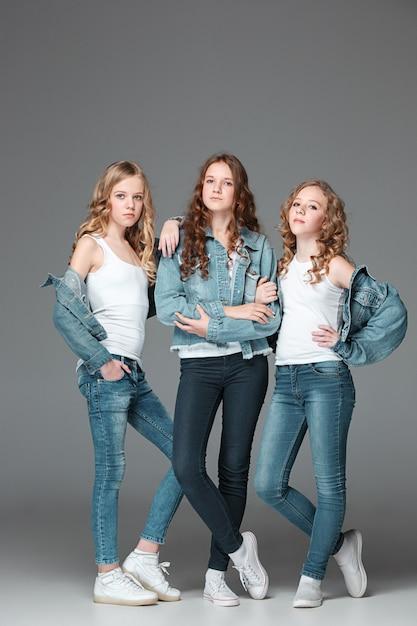Las chicas de moda de pie juntos y mirando a la cámara sobre fondo gris de estudio Foto gratis