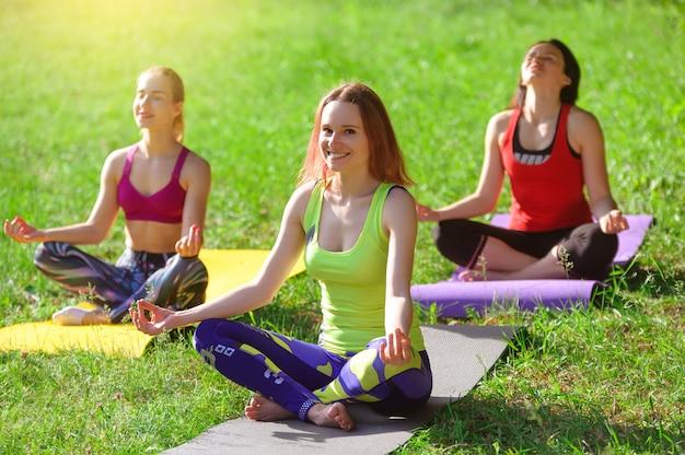 Chicas posando yoga afuera en el bosque por la mañana Foto Premium